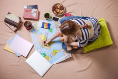 Young woman making marks on the map while sitting on the floor, view from above. Stock Image