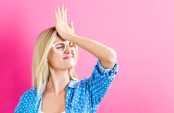 Young woman making a mistake. On a pink background Stock Photos