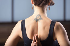 Young woman making namaste behind the back, studio evening pract. Young attractive woman practicing yoga, making namaste behind the back, working out, wearing stock image