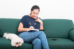 Young woman making notes in her journal. And relaxing at home on the couch Stock Photos