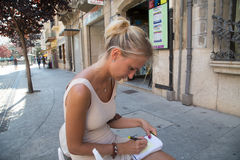 Young woman making notes in writing pad Stock Images