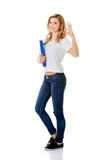 Young woman making ok sign holding binder Royalty Free Stock Photography