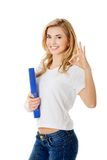 Young woman making ok sign holding binder Royalty Free Stock Photo