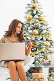 Young woman making online shopping near christmas tree Stock Image