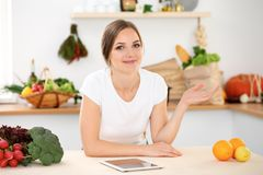 Young woman is making online shopping by tablet computer and credit card. Housewife found new recipe for cooking in a. Young woman is making online shopping by Royalty Free Stock Image