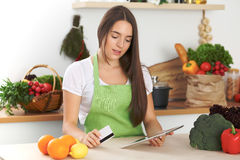Young  woman is making online shopping by tablet computer and credit card. Housewife found new recipe for  cooking in Stock Photo