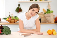 Young woman is making online shopping by tablet computer and credit card. Housewife found new recipe for cooking in a. Kitchen Royalty Free Stock Photos