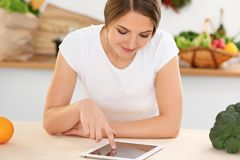 Young woman is making online shopping by tablet computer and credit card. Housewife found new recipe for cooking in a. Kitchen Royalty Free Stock Photo