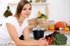 Young woman is making online shopping by tablet computer and credit card. Housewife found new recipe for cooking in a. Kitchen Royalty Free Stock Photography