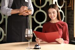 Young woman making order at restaurant. Young women making order at restaurant and waiter writing it down Stock Photography