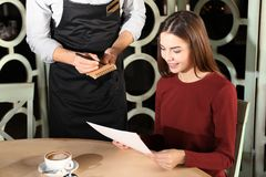 Young woman making order at restaurant. Young women making order at restaurant and waiter writing it down Royalty Free Stock Photos