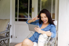 Young woman making peace hand sign with chat video Stock Photography