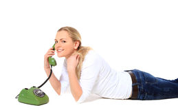 Young woman making phone call. Attractive young woman making phone call while lying on floor. All on white background Royalty Free Stock Photo