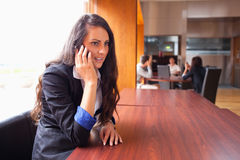 Young woman making a phone call. While her coworkers are in a meeting Stock Images