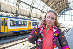 Young woman making a phone call at the central station in Amster Royalty Free Stock Image