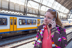 Young woman making a phone call at the central station in Amster Royalty Free Stock Images
