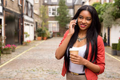 Young woman making a phone call. Young woman on the phone with a coffee Stock Photo