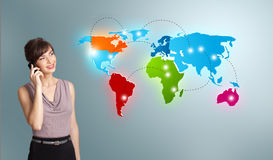 Young woman making phone call with colorful world map Stock Images