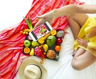 Young woman making photo of exotic fruits on the tray Royalty Free Stock Photo