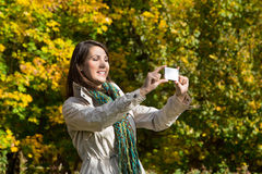 Young woman making a photo with her phone in autumn. Royalty Free Stock Photo