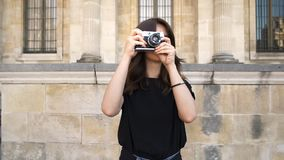Young woman making photo rewinding a film camera. Old buildings in Paris on background. Gimbal shot of young smiling happy caucasian brunette woman rewinding stock video