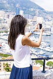 Young woman making photos  at Monte Carlo harbour in Monaco. Azur coast. Stock Images