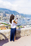Young woman making photos  at Monte Carlo harbour in Monaco. Azur coast. Stock Photo