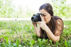 Amateur Photographer Nature. Young woman making picture of dandelion with vintage camera, female amateur photographer taking photo in nature royalty free stock images