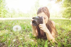 Amateur Photographer Nature. Young woman making picture of dandelion with vintage camera, female amateur photographer taking photo in nature royalty free stock photography