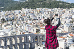 Young woman making pictures of the cityscape in Kavala,Greece Royalty Free Stock Photos