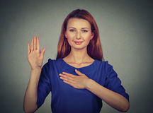 Young woman making a promise. Isolated on gray wall background royalty free stock photos