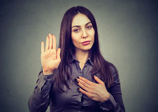 Young woman making a promise. Woman making a promise or testifies Stock Photos