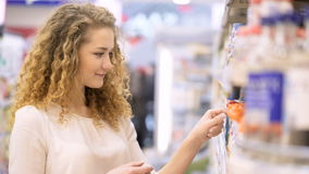 Young woman is making purchases in trade center. Cute 20s blonde lady with long curly hair make purchases in department store close up. Young mother select puree stock footage