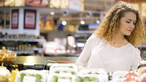 Young woman is making purchases in trade center. Cute 30s brunette lady with long curly hair make purchases in department store closeup. Sweet female buyer stock footage
