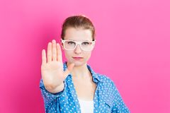 Young woman making a rejection pose. On a pink background Stock Images
