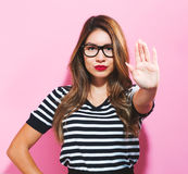 Young woman making a rejection pose. On a pink background Royalty Free Stock Photos