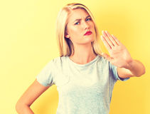 Young woman making a rejection pose. On a yellow background Stock Photo