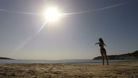 Young woman making relaxing exercises on the beach. Shoots against the sun. Young woman relax on the beach near the ocean. Woman with long hair makes relaxing stock footage