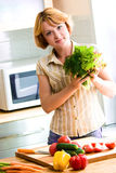 Young woman making salad. At domestic kitchen Stock Photography