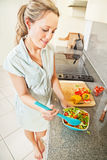Young woman making salad. Pretty young woman making salad in the kitchen at home Royalty Free Stock Photography