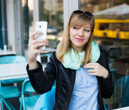 Young woman making self portrait using smartphone Stock Photos