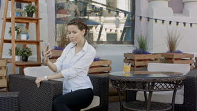 Young woman making self portrait using smartphone. girl making selfie. woman in cafe. woman alone. self portrait in cafe. Outdoors. smile. smilimg. gadget. self stock footage