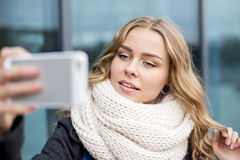 Young woman making a Selfe on a mobile phone portrait of a beautiful bright light on the street in autumn Royalty Free Stock Image