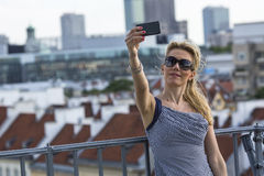 Young woman making selfie on cell phone on the background of the old town. Stock Images
