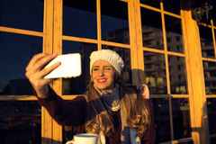 Young woman making selfie on her phone and wink Stock Photo