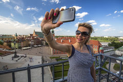 Young woman making selfie with smartphone on the background Warsaw Castle Square. Stock Photo