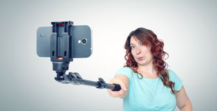 Young woman making selfie with a stick Royalty Free Stock Image