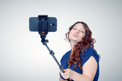 Young woman making selfie with a stick Stock Photography