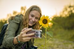 A young woman is making a selfie with a sunflower Stock Photo
