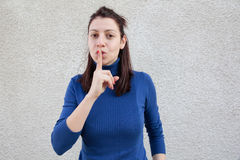 Young woman making silence sign. Serious young woman making silent sign with finger on mouth in front of grey wall Stock Photos
